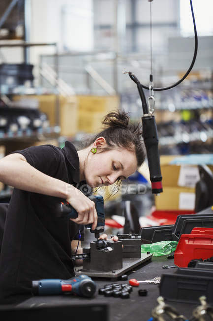 Young woman using a power tool — Stock Photo