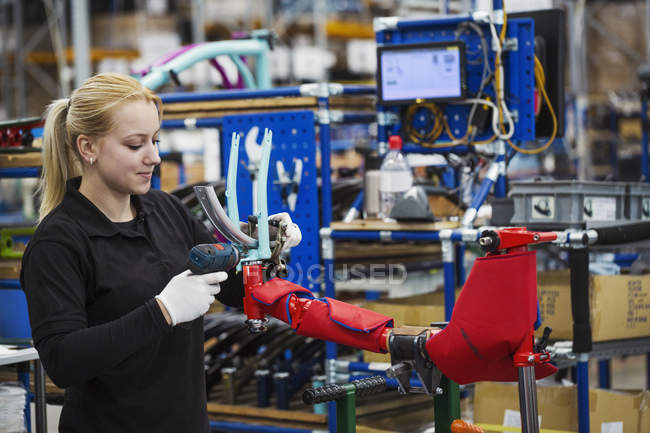 Factory worker assembling a bicycle — Stock Photo