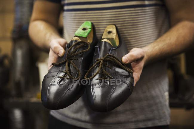 Man holding pair of shoes — Stock Photo