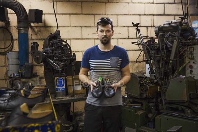 Человек, стоящий в сапожная мастерская — стоковое фото