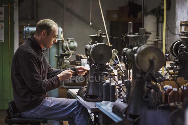 Man sitting at a sewing machine — Stock Photo
