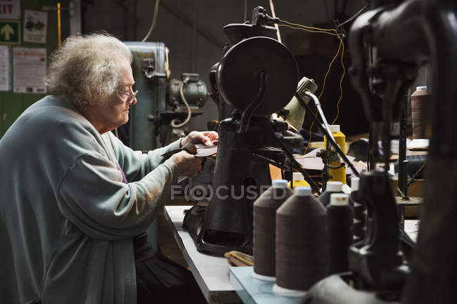 Older woman in a shoemaker's workshop. — Stock Photo