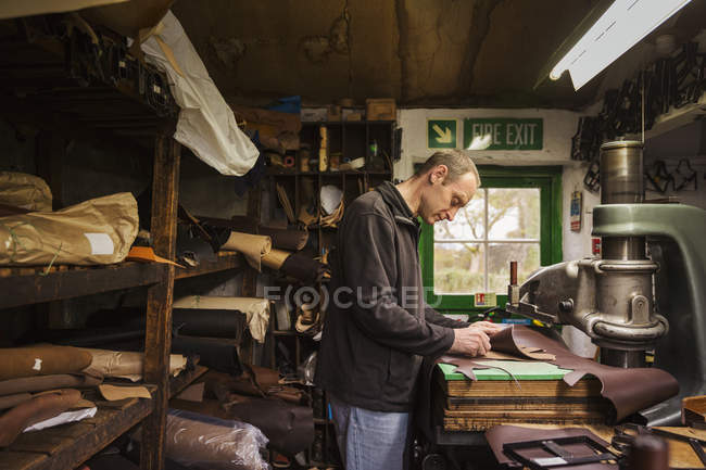 Uomo in piedi in una bottega di calzolaio — Foto stock
