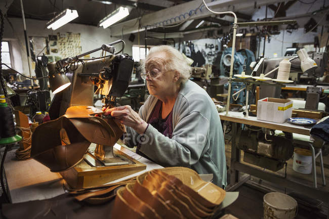 Older woman in shoemaker's workshop. — Stock Photo