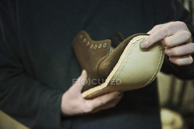 Worker attaching sole to leather boot. — Stock Photo