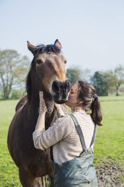 Woman kissing a brown horse — Stock Photo