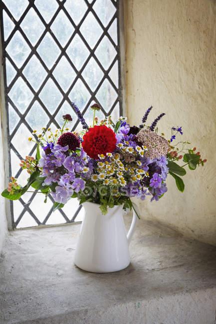Bouquet de fleurs dans une cruche blanche — Photo de stock