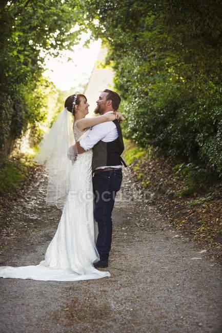 Newlyweds standing outdoors — Stock Photo