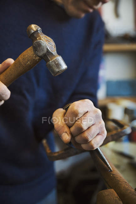 Man holding hammer and wood chise — Stock Photo