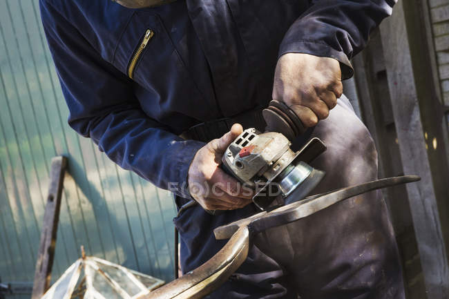 Mann arbeitet an Mistgabel aus Metall — Stockfoto