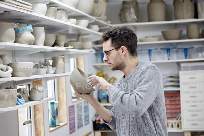 Hombre inspeccionando una cazuela de barro - foto de stock