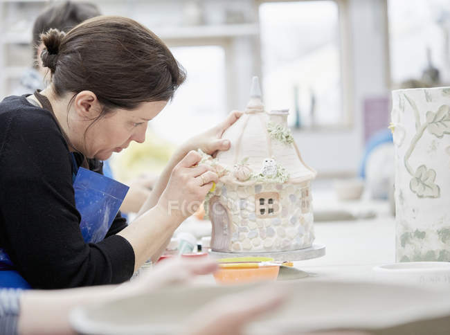 Woman working on decorated pottery cottage — Stock Photo