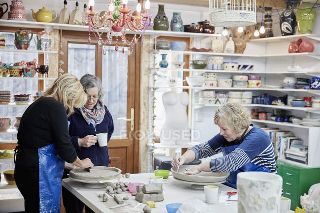 Three women in a pottery studio — Stock Photo
