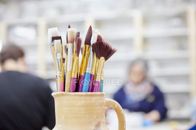 Pottery jug with paintbrushes. — Stock Photo