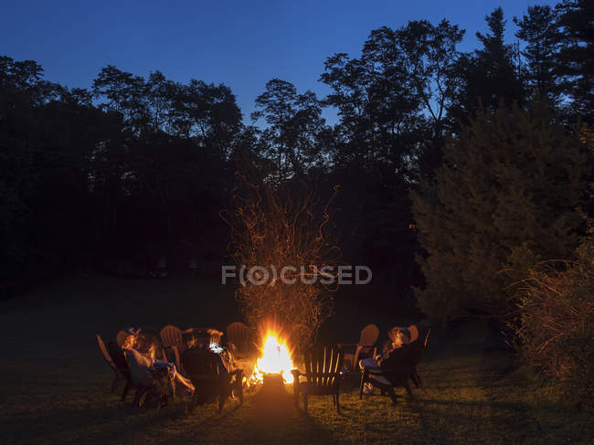 People seated around campfire — Stock Photo