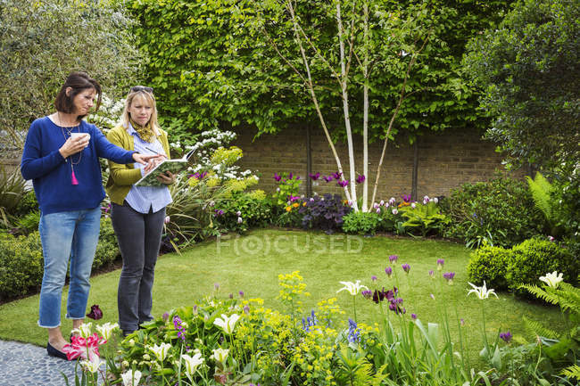 Women standing in a garden — Stock Photo