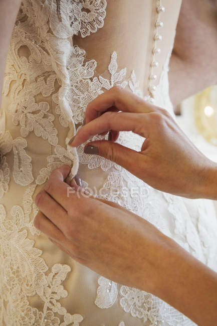 Dressmaker taking in wedding dress — Stock Photo