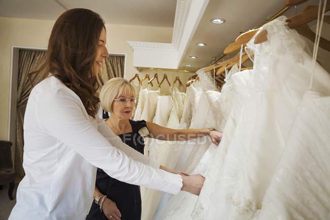 Femmes à la recherche par le biais de rails de robes — Photo de stock