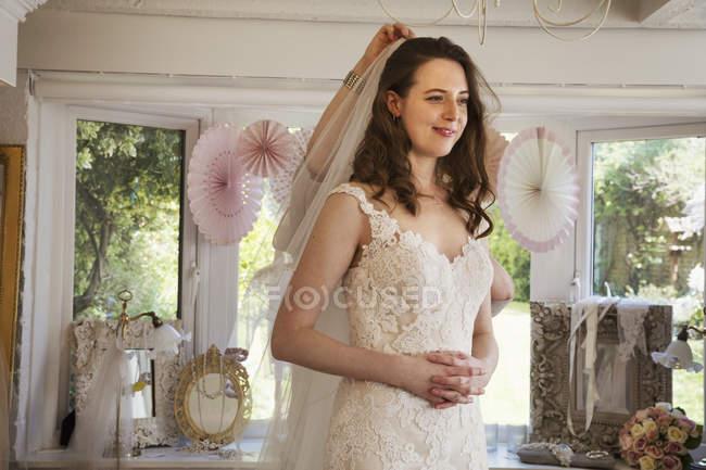 Jeune femme essayer des robes de mariée — Photo de stock