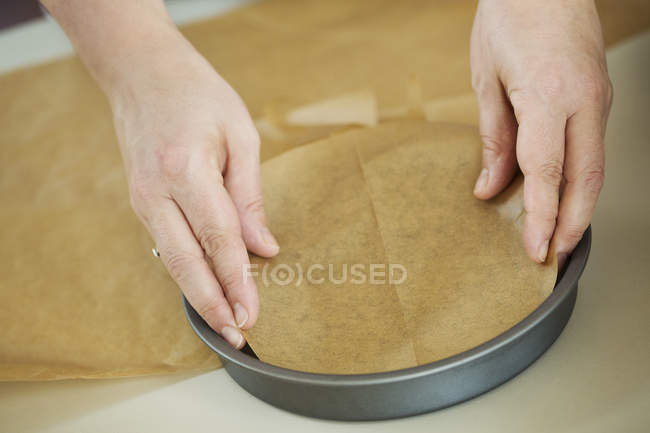 Person lining baking paper. — Stock Photo