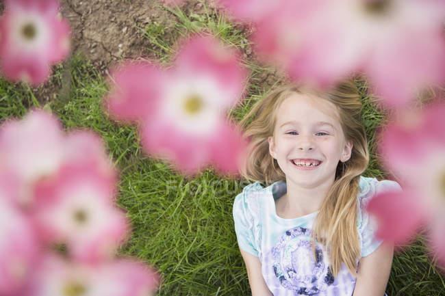 Jeune fille regardant à travers la fleur — Photo de stock
