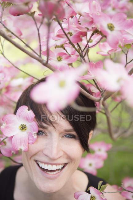 Mulher olhando através de ramos floridos — Fotografia de Stock