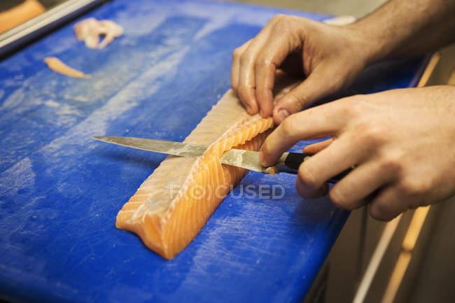 Cortar un filete de salmón - foto de stock
