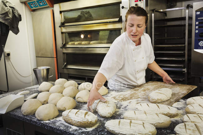 Woman placing freshly baked loaves — Stock Photo