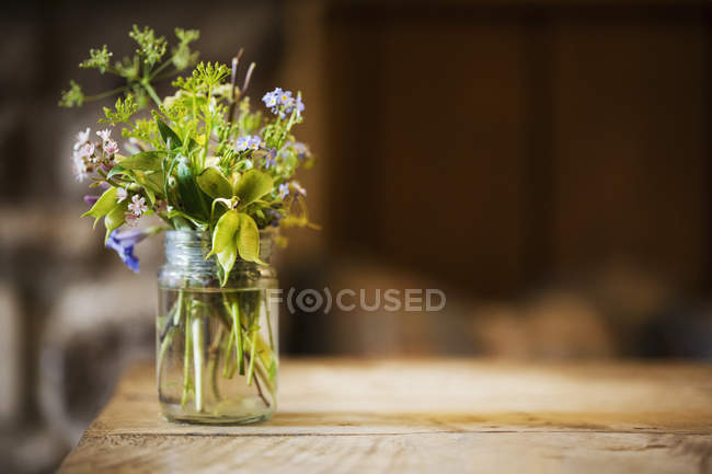 Glass jar with wild flowers — Stock Photo