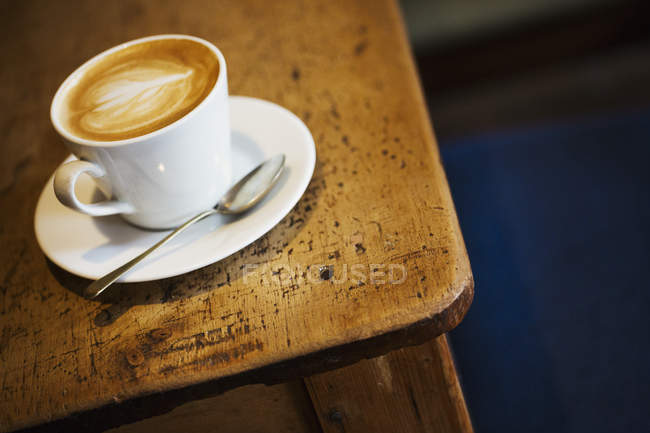 Cup of cappuccino on rustic wooden table — Stock Photo