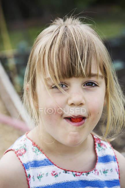 Menina sorridente, comendo um morango — Fotografia de Stock