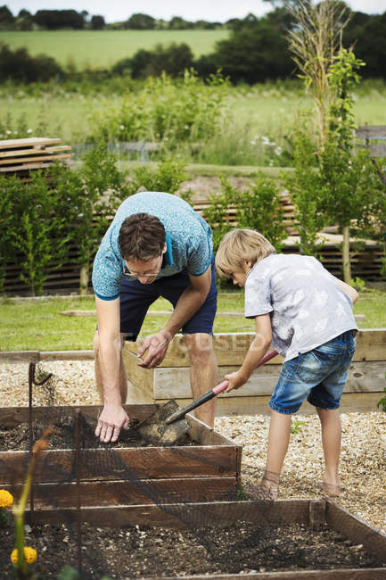 An and boy standing at plant bed — Stock Photo