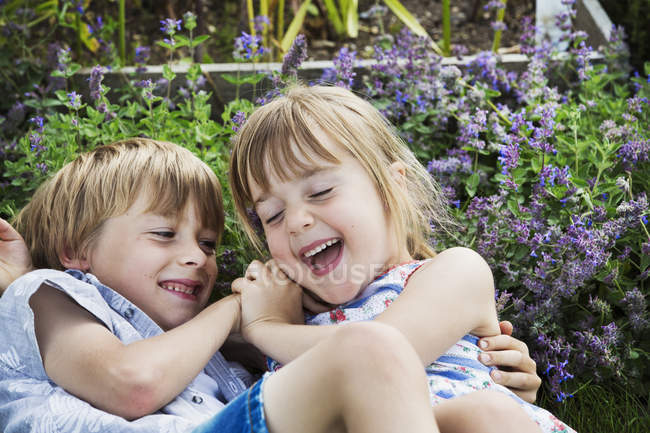 Smiling boy and girl roughousing — Stock Photo