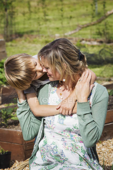 Son kissing mother on cheek. — Stock Photo
