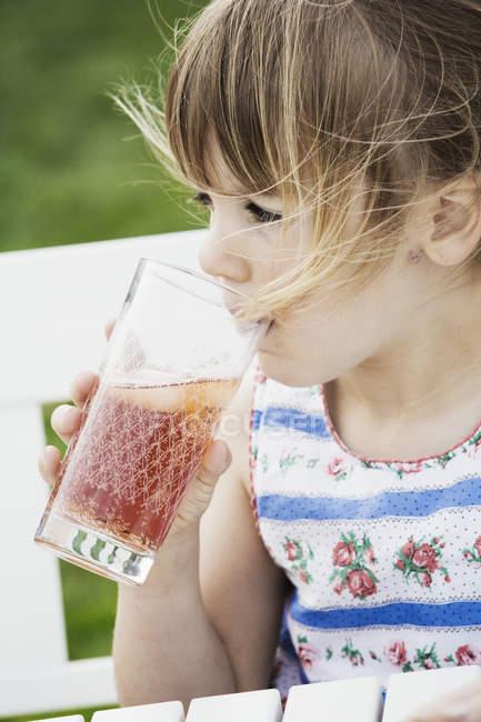 Девушка потягивает из стакана . — стоковое фото