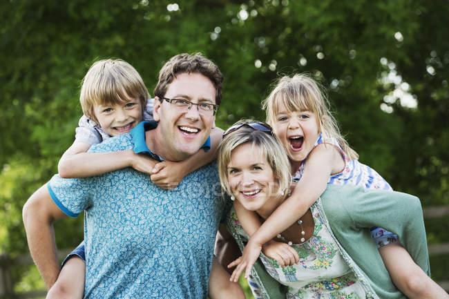 Pais dando sobreposto filho e filha — Fotografia de Stock