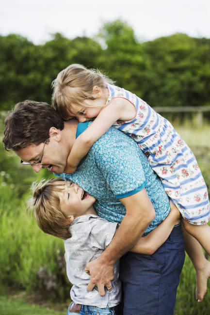 Father and two children in a garden — Stock Photo