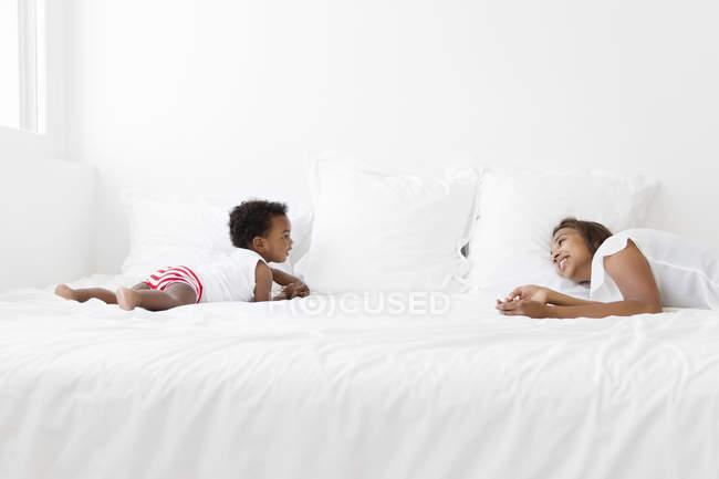 Жінки грають на ліжку з молодим хлопчиком — стокове фото