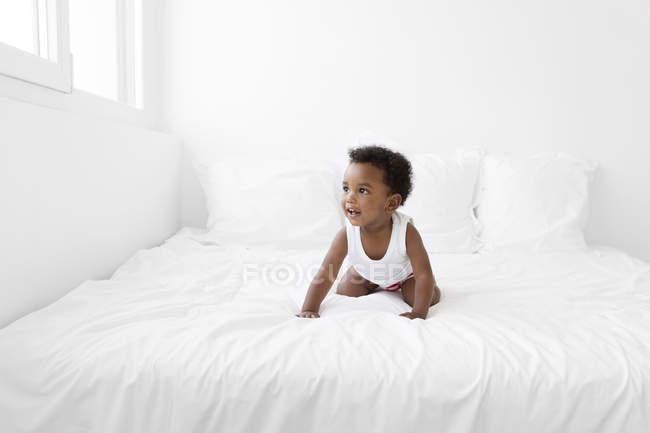 Хлопчик на колінах на ліжку — стокове фото