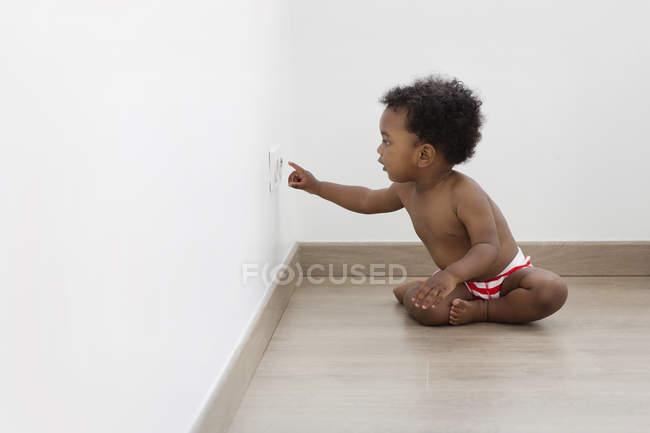 Хлопчик простягає руку до розетки — стокове фото