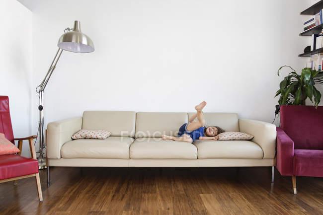 Girl lying on sofa with raised leg — Stock Photo
