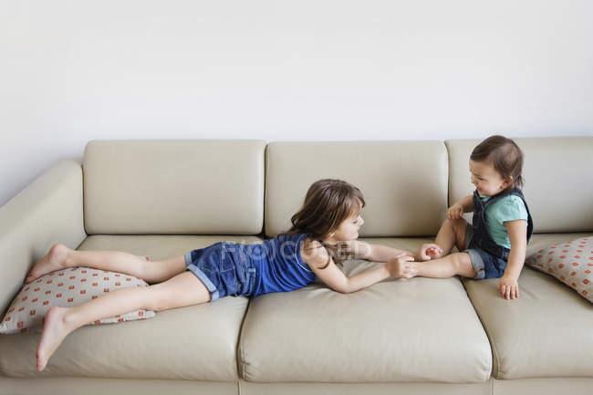 Молодий хлопчик і дівчинка, граючи на дивані — стокове фото