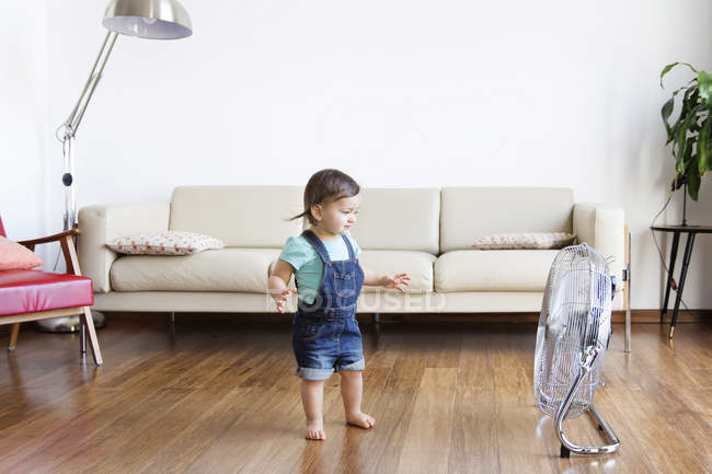 Boy standing in front of electric fan — Stock Photo