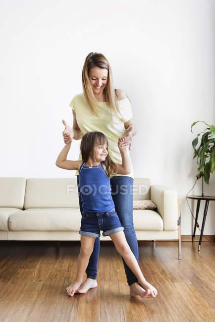 Girl balancing on womans feet — Stock Photo