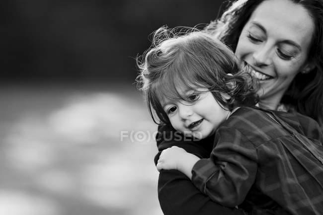 Улыбающиеся женщина, держащая молодая девушка — стоковое фото