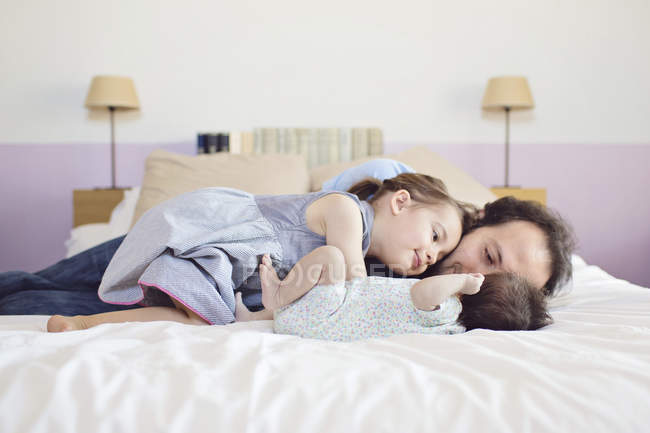 Man girl and newborn lying on bed — Stock Photo