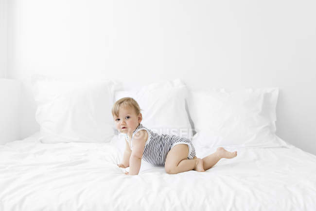 Baby boy lying on bed with duvet — Stock Photo