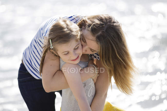 Blond woman hugging girl on beach — Stock Photo