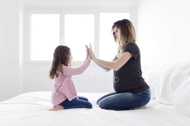 Schwangere Frau und Mädchen kniend auf Bett — Stockfoto