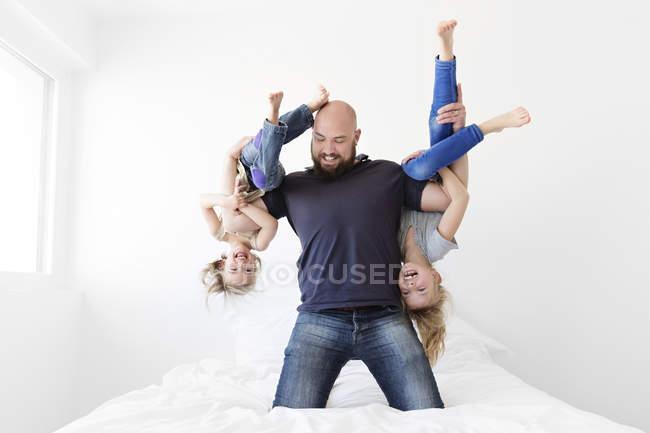 Mann kniet auf Bett hält ein Mädchen — Stockfoto